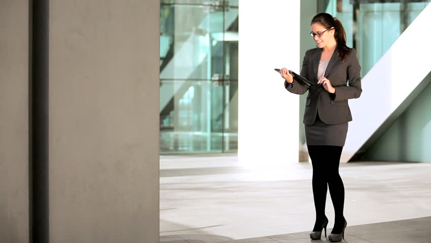 Smart young businesswoman in the atrium of a modern office building using a modern wireless tablet | Shutterstock HD Video #1334566