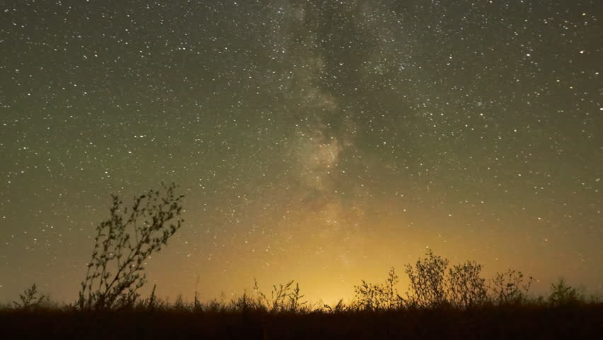 Night sky of stars time-lapse - Milky Way and glow above grass field, star and airliner trails