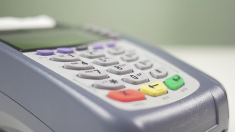 Paying with a credit card on a store terminal and entering the PIN number to complete the transaction. Great to illustrate a shopping experience.