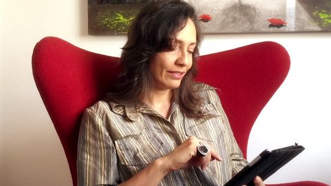 Mature brazilian woman sitting in armchair using tablet computer