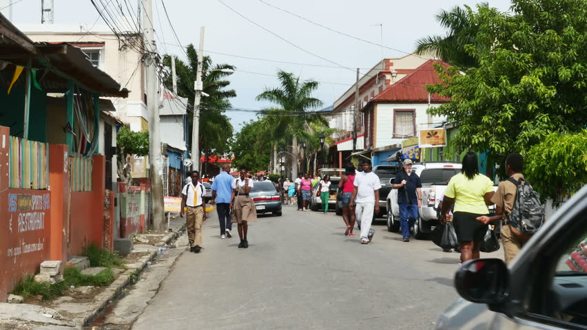 FALMOUTH, JAMAICA - NOVEMBER 15, 2015:Pedestrian and auto traffic clog a narrow Jamaican street during a daily commute in this port city in the Caribbean