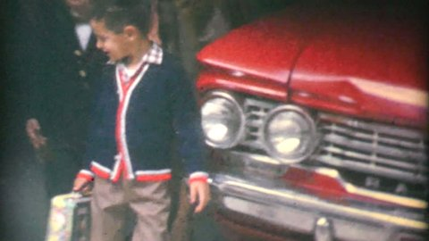 TRENTON, NEW JERSEY, SEPTEMBER 1965: A couple of friends stand in front of a car with their lunch boxes eager to start their first day of school in the fall of 1965.