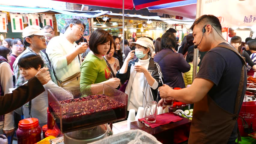 TAIPEI, TAIWAN - FEBRUARY 16, 2015: Barker treats with compote people in the market, live crowded place. Traditional market lifestyle view. Fresh fruit-drinks stall on the crowded market | Shutterstock HD Video #13399316