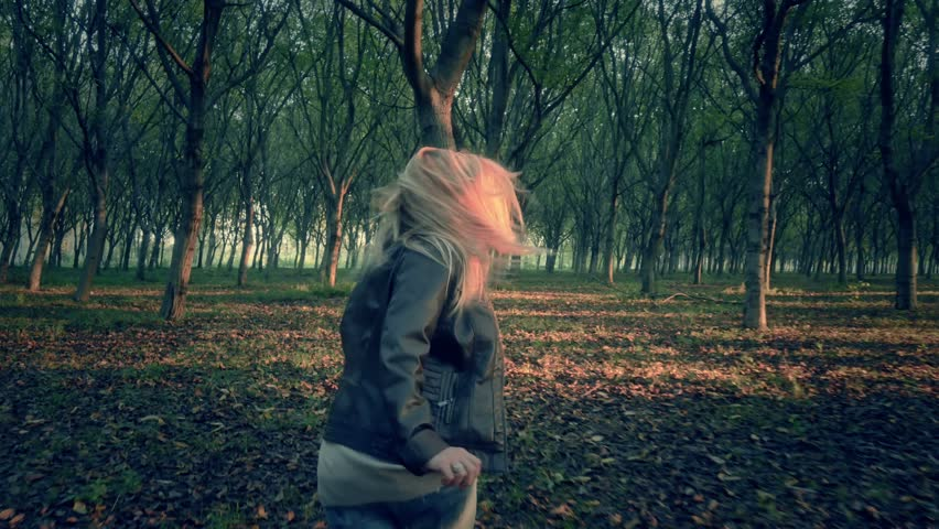 scared afraid female woman runs away escape from murderer chasing her through a dark forest full of trees looking for help horror scene
