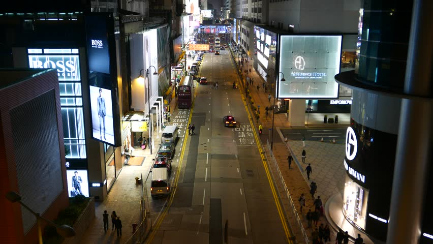 HONG KONG - FEBRUARY 18, 2015: Canton road top perspective in night time, luxury shops area, tourists attraction place. Small traffic at late evening, several taxi cars, people walk at sideway.   Shutterstock HD Video #13422581