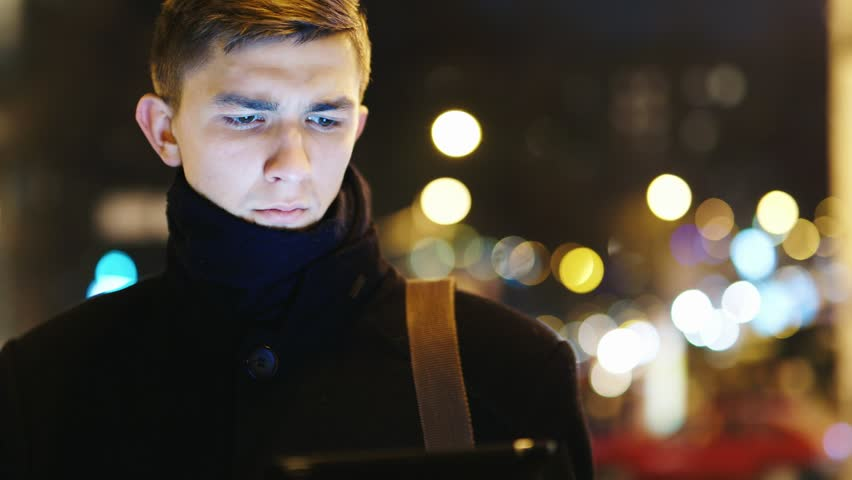 The young man with the tablet against the evening city | Shutterstock HD Video #13435016