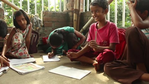 Simple, sweet Indian boys and girls smile, laugh and draw happily with each other in a rural school in Bengal