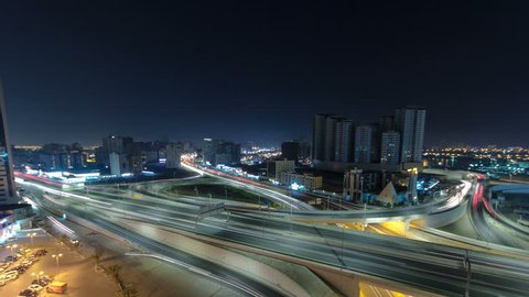 Cityscape of Ajman with traffic on main road overpass from rooftop at night with lights timelapse. Ajman is the capital of the emirate of Ajman in the United Arab Emirates. 4K
