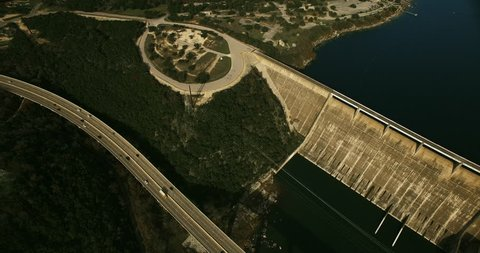 The camera slowly pans left to right and tilts up to reveal a beautiful Lake Travis and Mansfield Dam in Austin, Texas.  Traffic is seen crossing the bridge in the foreground.