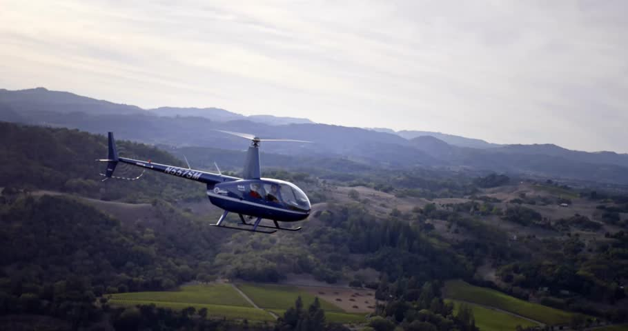 SONOMA CA, OCT 26, 2015: Close up shot of helicopter flying over vineyards and forest. Helicopter banks away from frame with passengers. (Sonoma County, CA - 10-26-2015) | Shutterstock HD Video #13451096