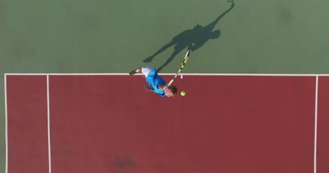 Overhead shot. Serve with professional tennis player. Top view from the quadrocopter. 4K
