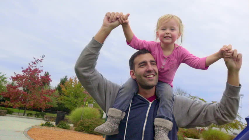 Cute little girl acts like superwoman flying on her dads shoulders