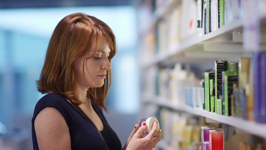 Attractive young woman buying cosmetic products / Looking at the shelf and choosing a hand cream - lifestyle sequence