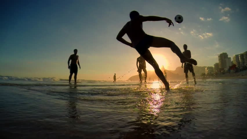 Silhouettes of carioca Brazilians playing altinho beach football at sunset on Ipanema Beach in Rio de Janeiro, Brazil #13465346