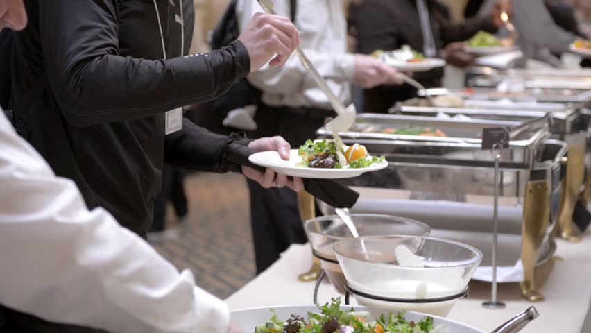 Guests attending a corporate business seminar in a hotel help themselves to the free lunch at the catered buffet table.   Shutterstock HD Video #13498856
