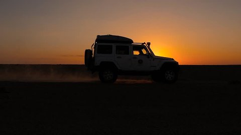driving off-road car in the sahara desert at sunset