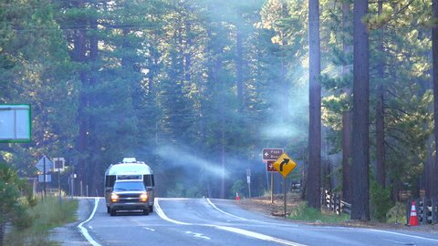 CIRCA 2015 - A truck tows an airstream trailer down a foggy forest road.