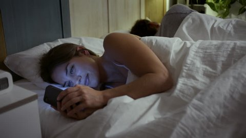 Young woman texting to her lover in the bed while her boyfriend is sleeping. Cheating.