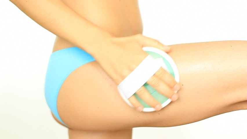 Woman doing anti-cellulite massage to her thigh, isolated on white