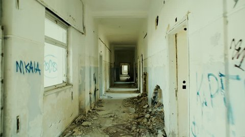 4K UHD Walking through an abandoned long corridor.Gimbal/steadycam stabilized pov shot of someone walking inside a very long corridor of a destroyed sanitorium.Destruction and abandonment