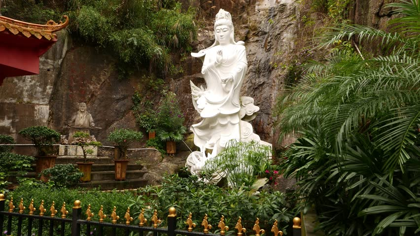 HONG KONG   FEBRUARY 23, 2015: White Buddga Ride Dragon, Statue In Garden,  Against Stony Wall Waterfall. White Statue Of Kuan Yin Riding Dragon, ...