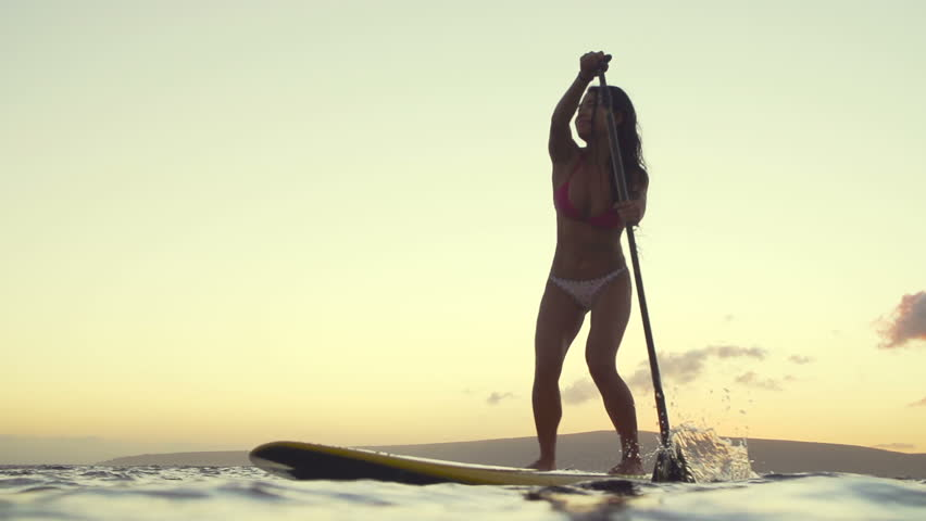 Young Woman Stand Up Paddling Boarding At Sunset