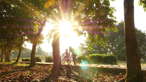 Asian daughter practice to ride a bicycle with her father, Happy family in the park, 4K Video