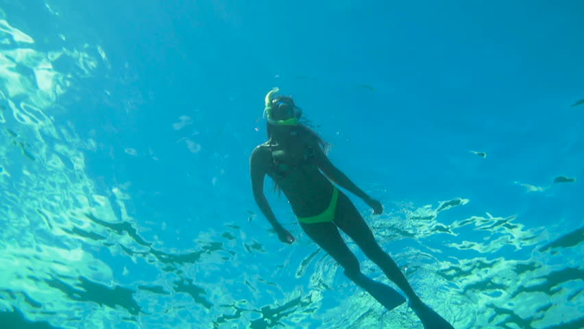 Underwater Angle Looking Up Of Woman Snorkeling In Blue
