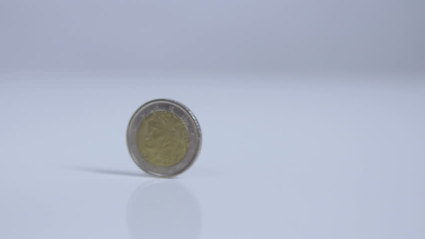 Two-Euro coin rolling in one place, on white surface slow motion  | Shutterstock HD Video #13659536