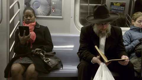 NEW YORK - DEC 7, 2015: black woman reading kindle sitting next to Jewish man in hat with Torah, riding subway train together, racial harmony, 4K NY. People read religious texts while in transit.
