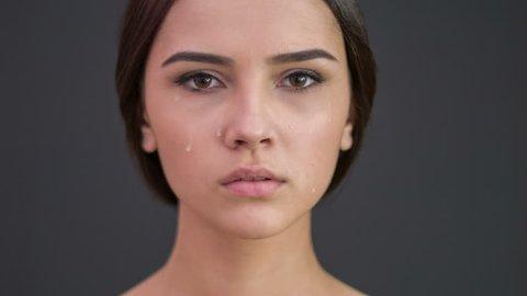 Young sad woman spills tears.