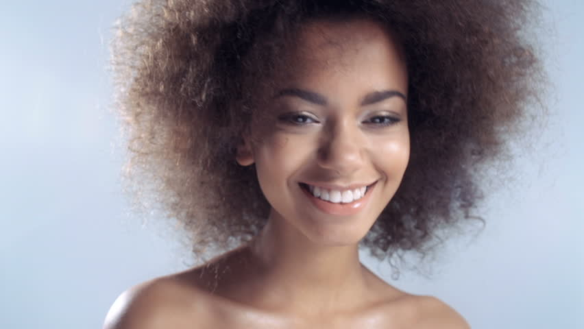 Portrait of a beautiful cheerful young African woman smiling over white background.