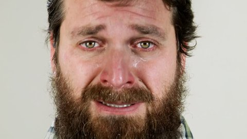 Extreme close up of hipster crying against neutral background
