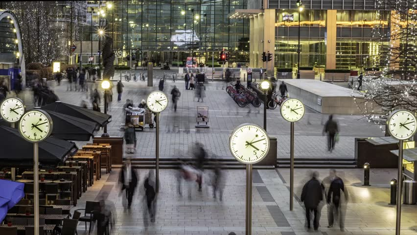 Timelapse of people rushing from work with several clocks in the docklands financial centre in London