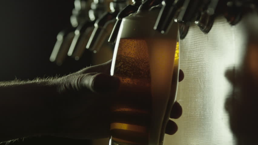 CU SLO MO SELECTIVE FOCUS Man pouring beer from tap and spilling froth