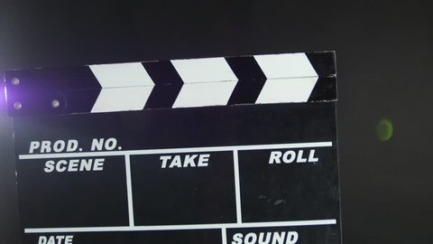 Hands holding a film clapper board, on black, close up, back light