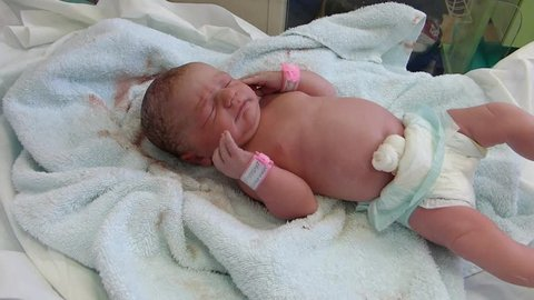 New-born baby and nurse's hands