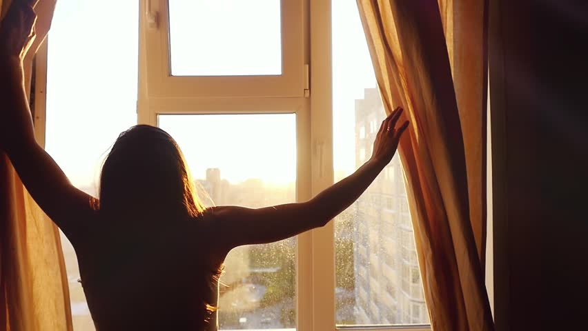 Attractive young woman is open curtains,  looking at amazing sunset above urban city standing near the window  in slowmotion #13839836