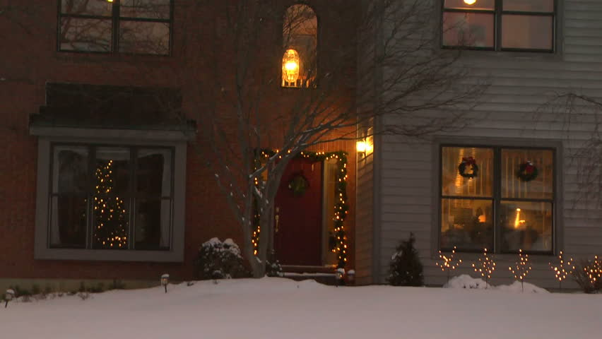 Establishing shot of middle class house; Christmas time on a snowy evening. Christmas lights and a Christmas tree.  Snow on the ground and roof.  Part of a set of the same house in all seasons.