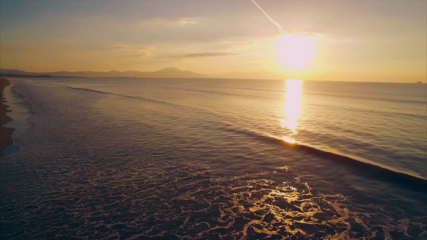Scenic drone footage of waves reaching beach during sunset. Slow motion tilt up shot of beautiful sea and sun. Reflection of sunlight is falling in seascape | Shutterstock HD Video #13863806
