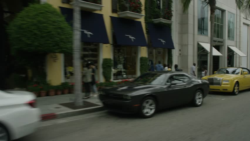 Beverly Hills: Los Angeles, CA USA Set 3 - Driving Plate Right Rear three quarters View: Car travels N on Rodeo Dr on a cloudy day in light traffic. Shot on RED Dragon.