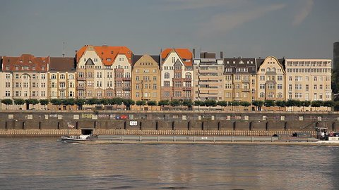 Old buildings near the river in Europe, ships are sailing