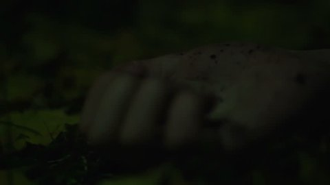 Close-up of person's hand convulsing, maniac strangling victim in dark forest