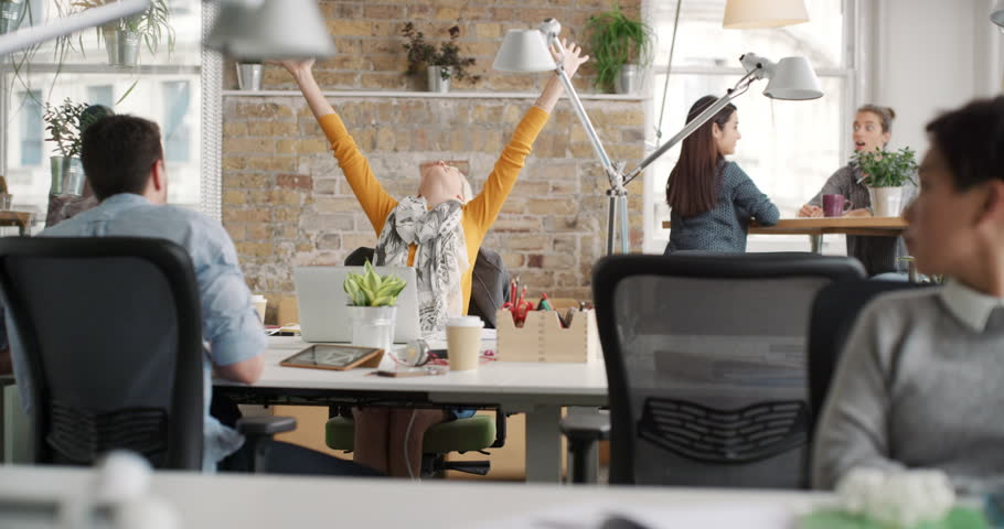 Business woman with arms raised celebrating success watching sport victory on laptop diverse people group clapping expressing excitement in office | Shutterstock HD Video #13947476