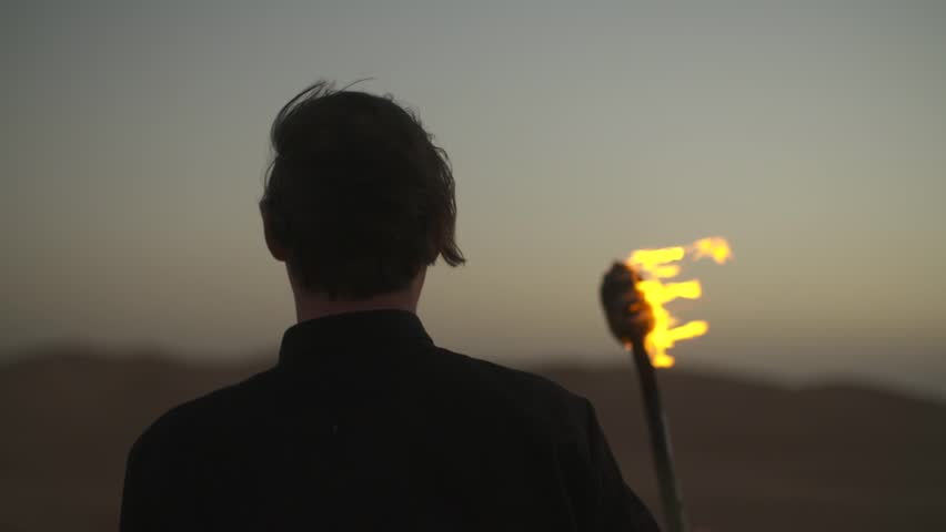 A person holding a flaming torch while looking out into the desert night