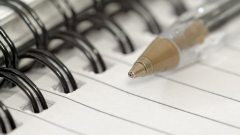 Pen and Notepad extreme close up HD stock footage. A pen on an open paged notepad in true macro close up with a slow rotational camera move.