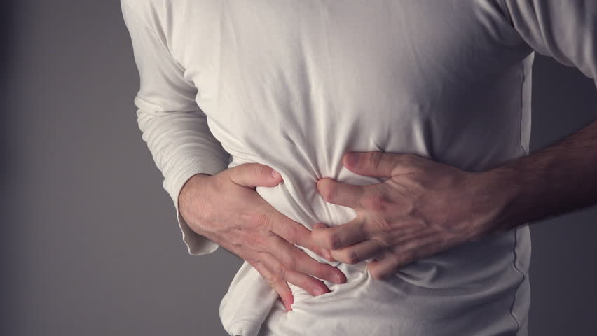Severe abdominal pain, man suffering from stomach ache, holding his belly and having painful cramps.