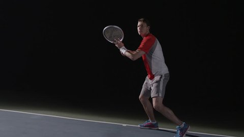 A nice forehand then backhand swing on a tennis court at night, man playing tennis
