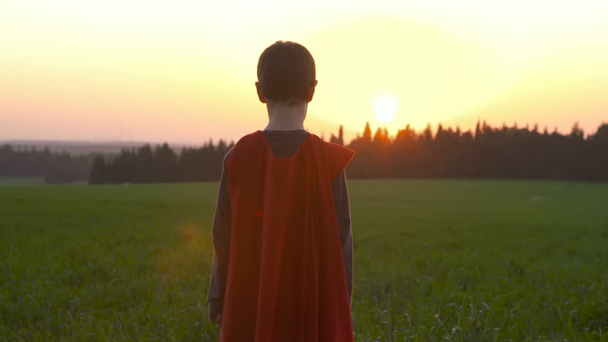 Boy dressed with a Superman cape running in a field, looking into the sunset