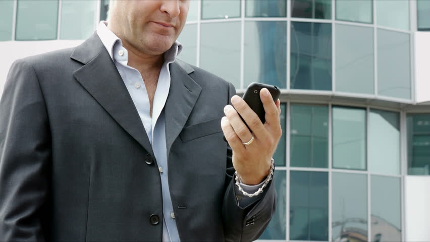 Happy businessman with mobile telephone or smartphone, visiting web site and browsing the internet near office building. People, manager, technology, smartphone